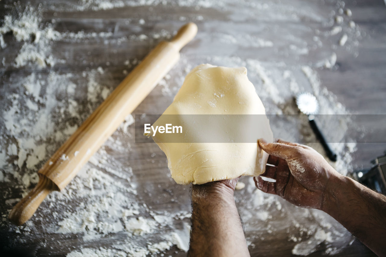 Cropped Hands Of Man Preparing Dough On Table
