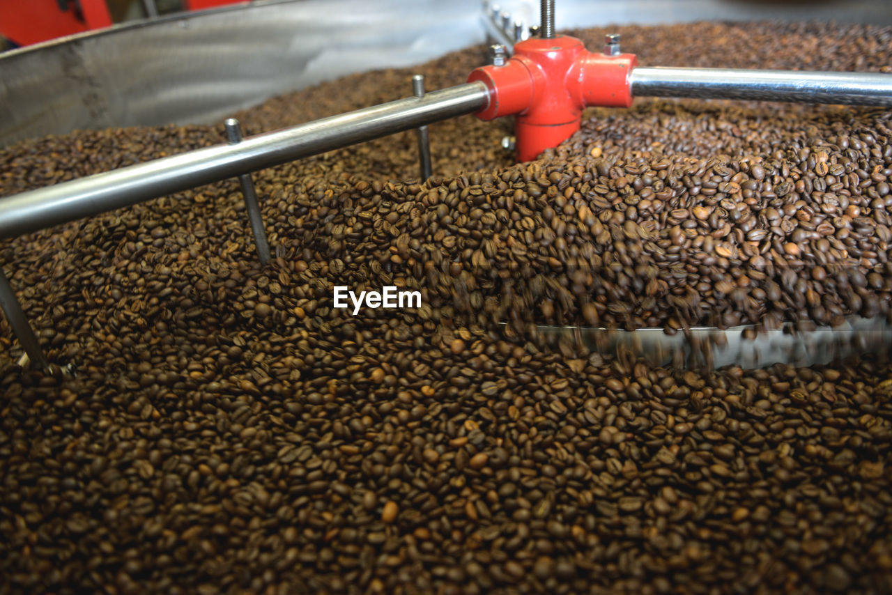 food and drink, roasted coffee bean, abundance, food, brown, freshness, coffee - drink, industry, no people, large group of objects, machinery, occupation, day, nature, high angle view, indoors, business, close-up, coffee, metal, caffeine