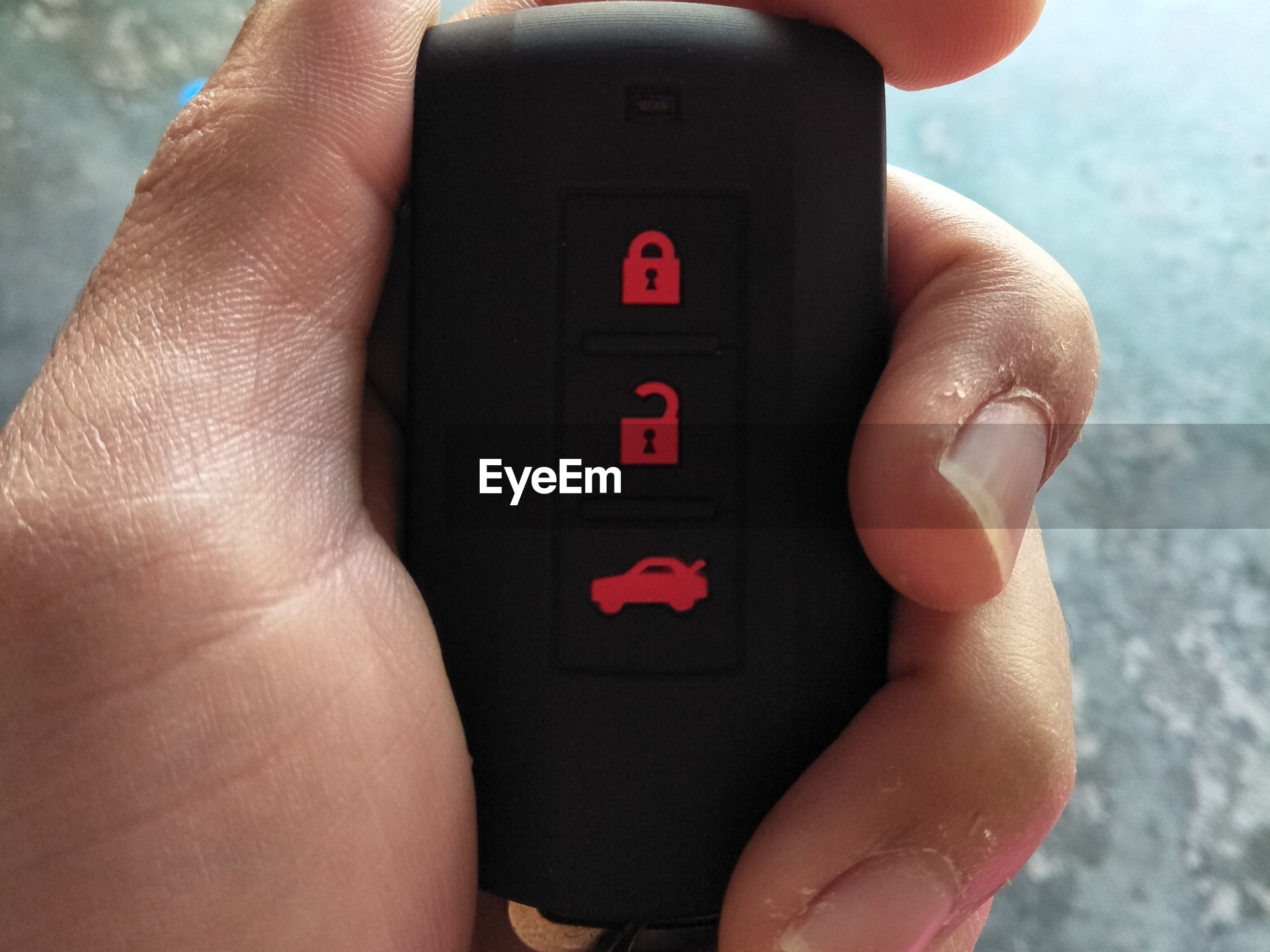 Close-up of hand holding car key