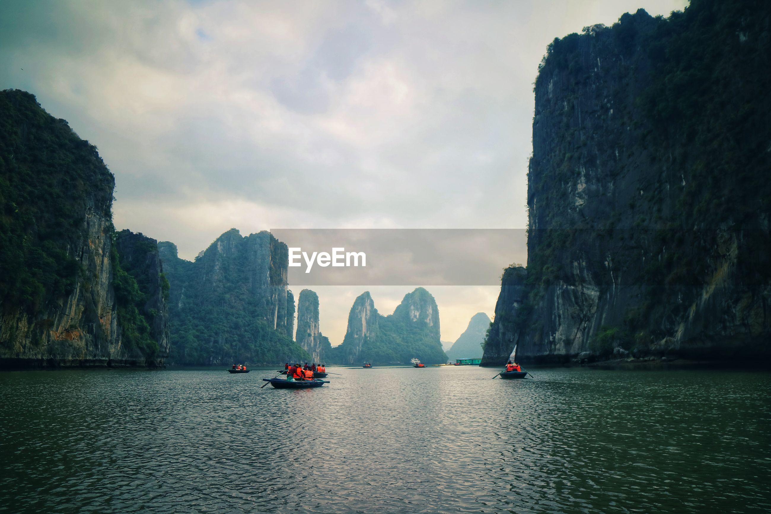 People kayaking on lake by mountains