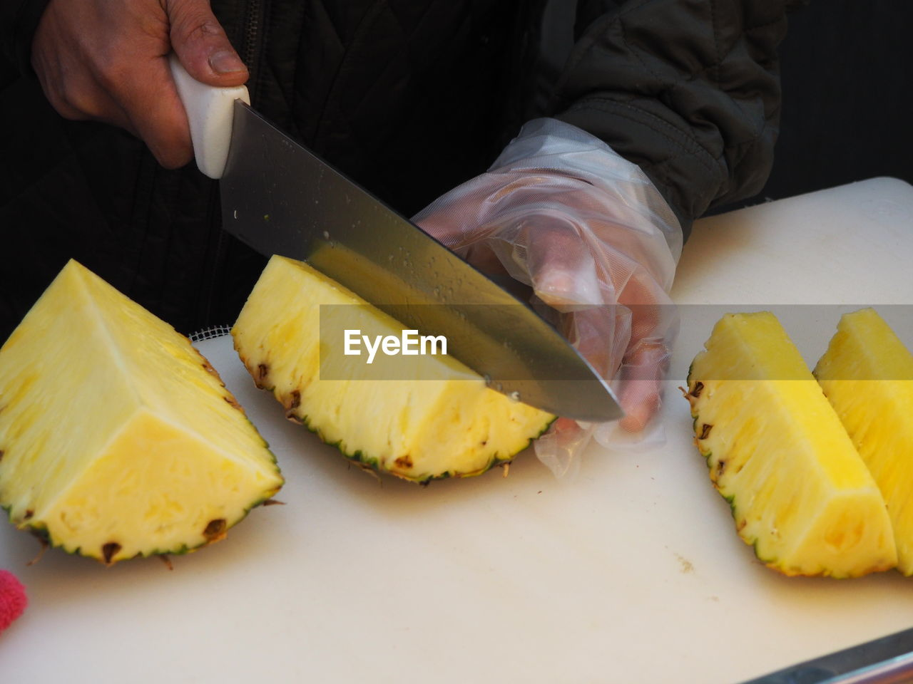 Cropped Image Of Male Vendor Cutting Pineapple On Board