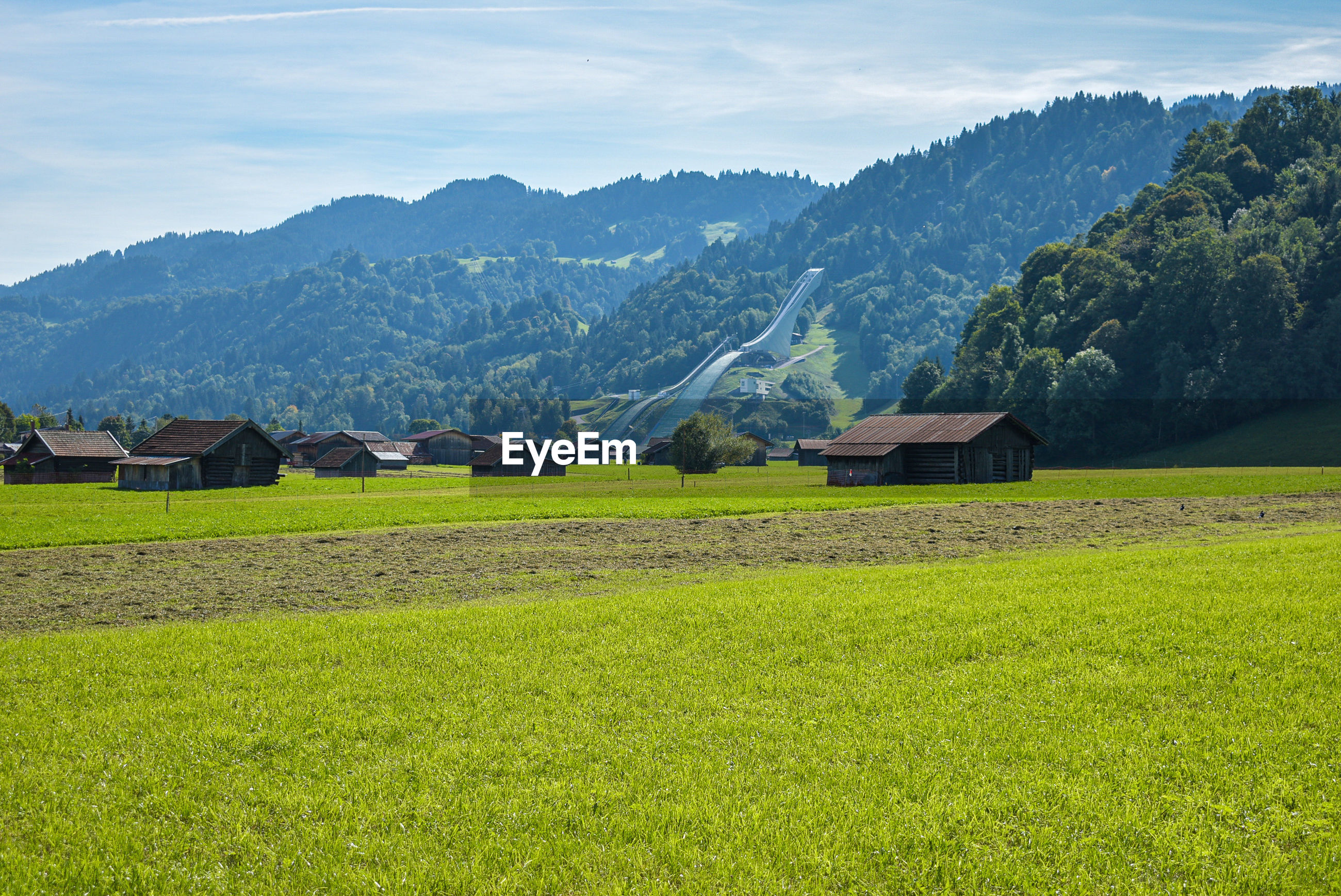 Scenic view of agricultural field by houses and mountains against sky