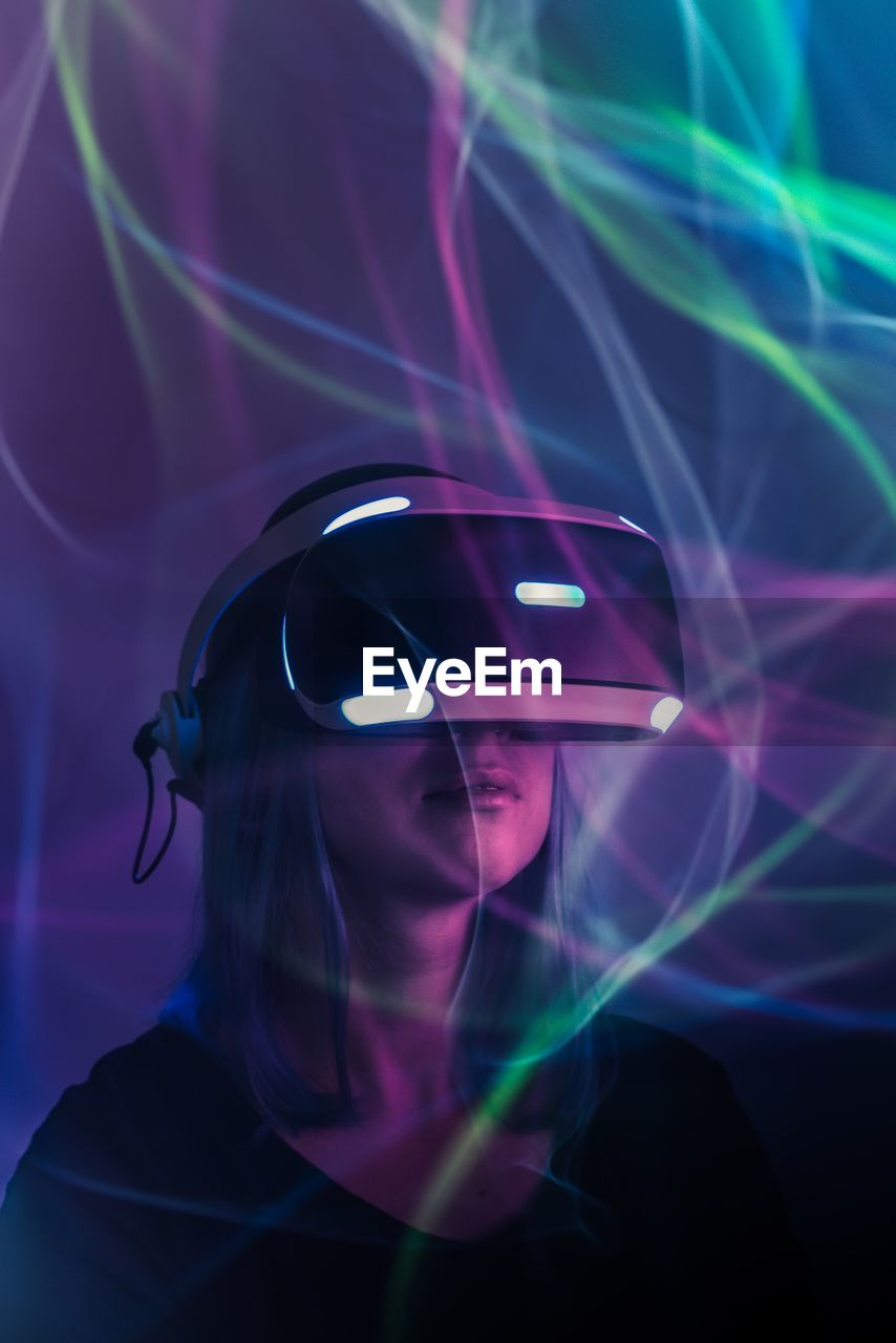 Woman using virtual reality simulator by light paintings