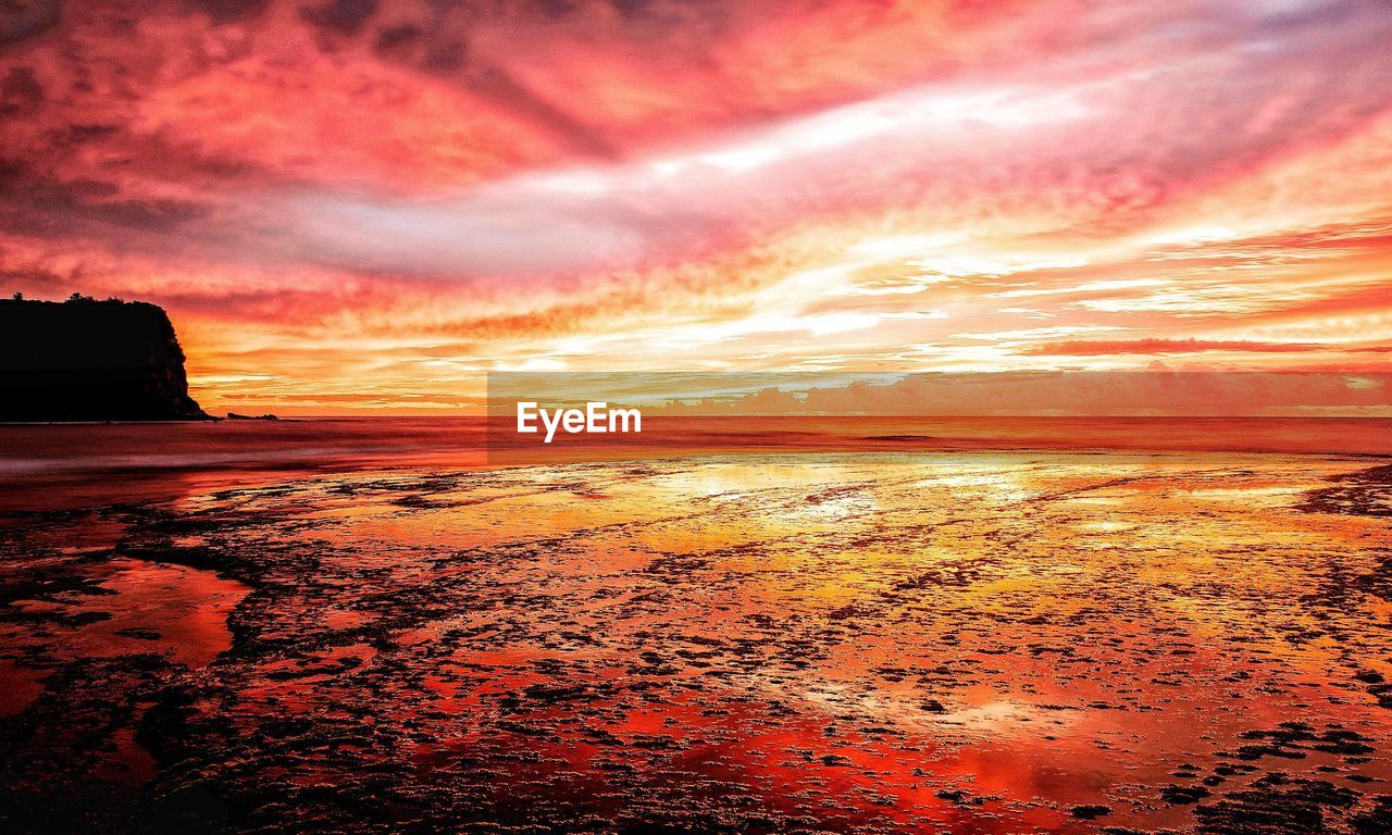 sunset, sky, beach, sea, orange color, beauty in nature, nature, dramatic sky, scenics, cloud - sky, tranquil scene, tranquility, water, no people, sun, outdoors, sand, horizon over water, wave