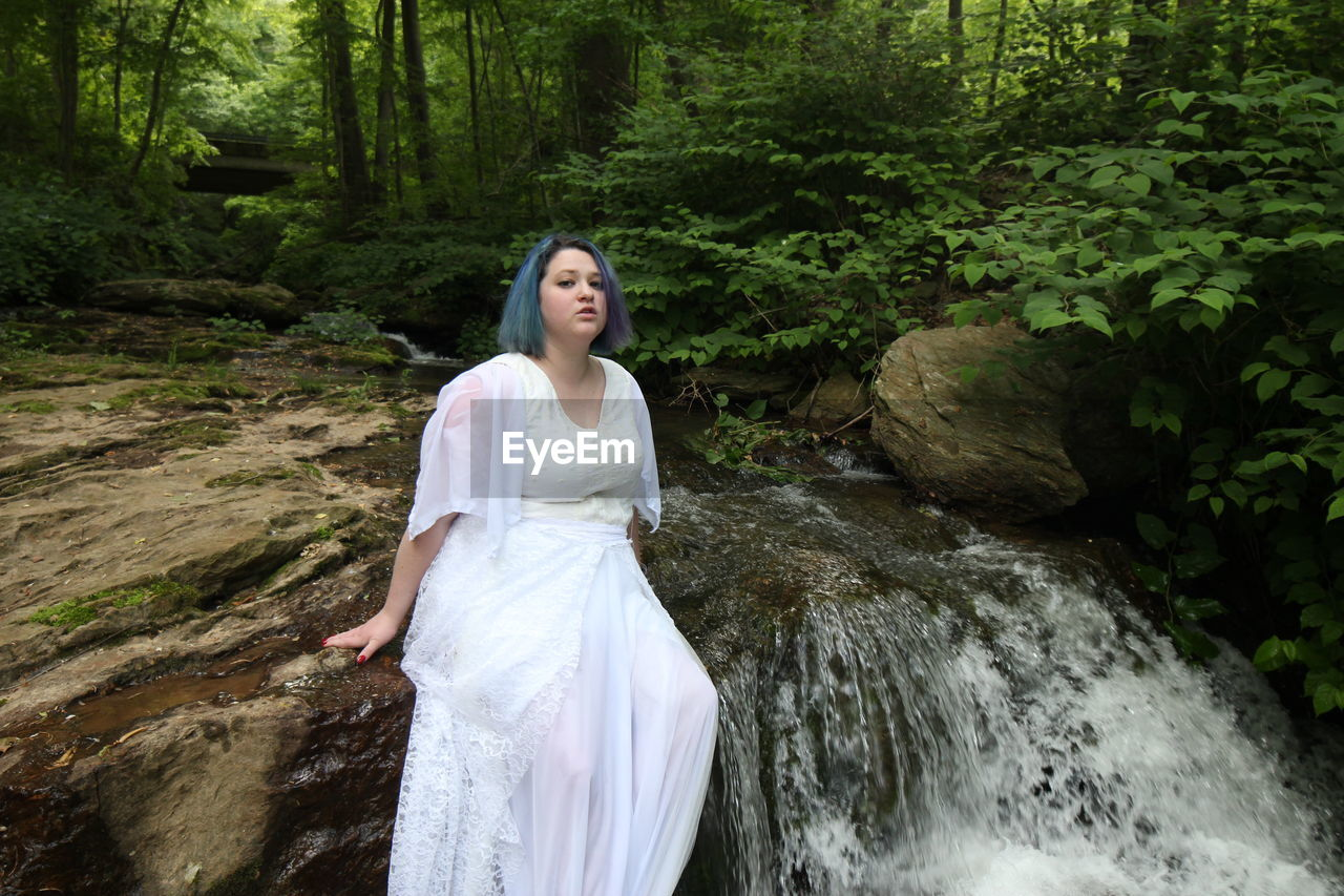 one person, young adult, leisure activity, forest, three quarter length, adult, real people, women, standing, water, nature, plant, tree, young women, lifestyles, land, white color, portrait, hair, outdoors, beautiful woman, hairstyle