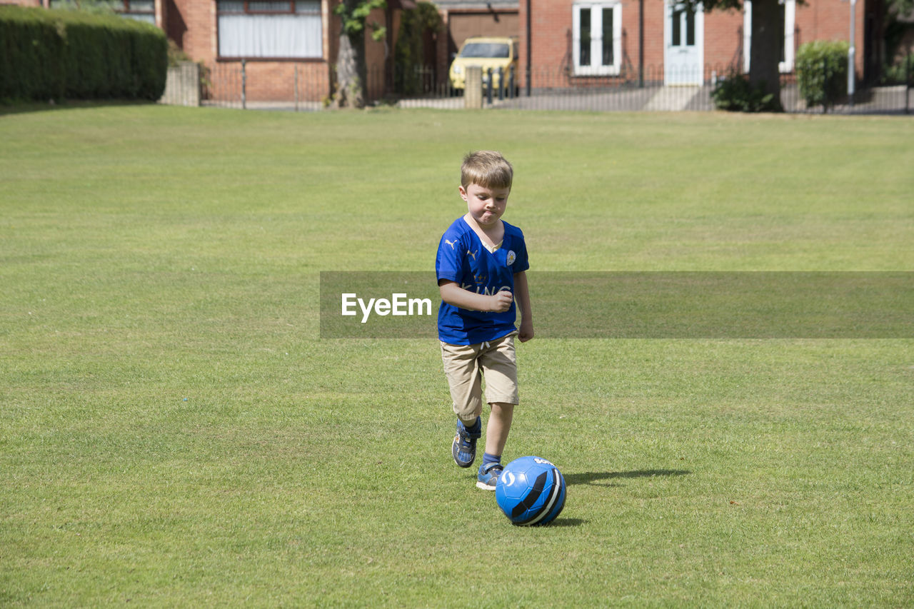 grass, child, childhood, full length, boys, soccer, sport, offspring, one person, soccer ball, males, team sport, day, ball, men, nature, sports equipment, plant, motion, outdoors, shorts