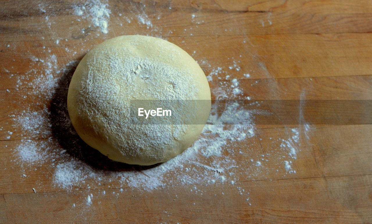 High Angle View Of Pizza Dough With Flour On Cutting Board