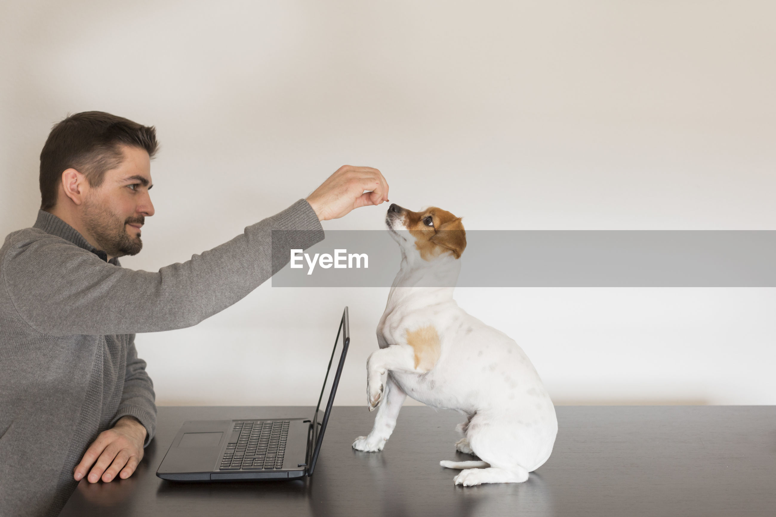 Man with dog on table against wall