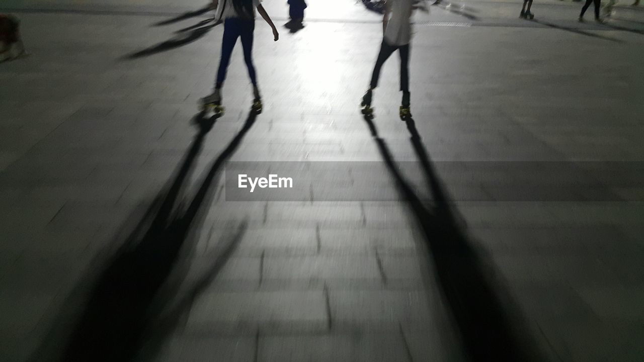 Low section of people skating on street at night