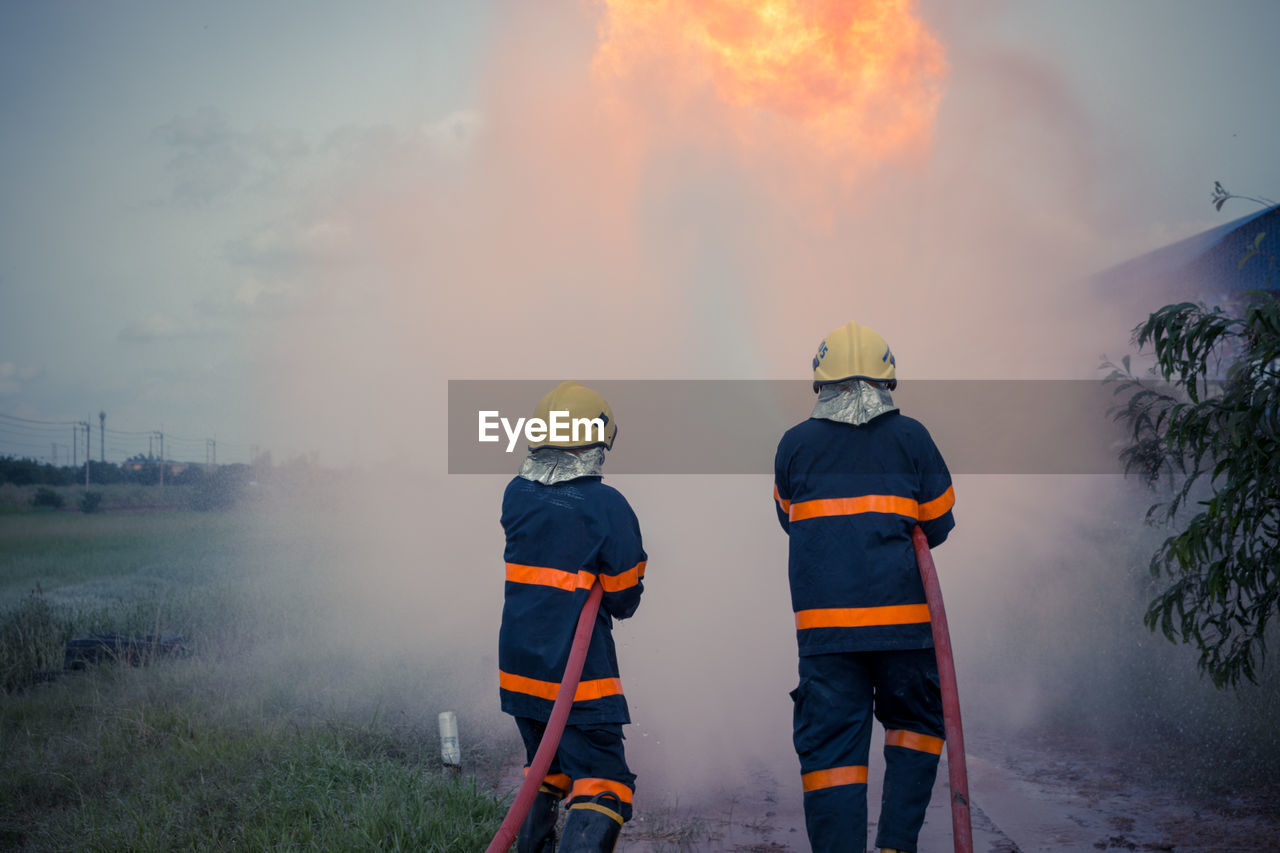 Firefighters Spraying Water While Standing On Field