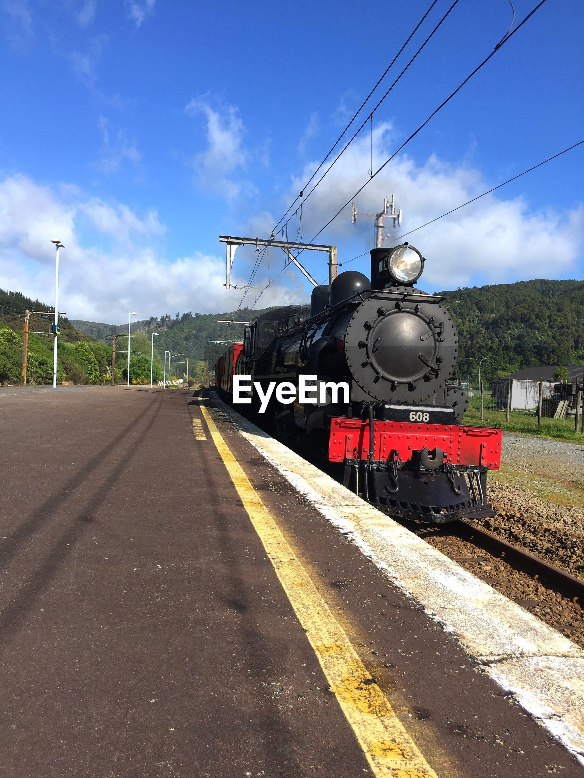 Steam train on railroad track against sky