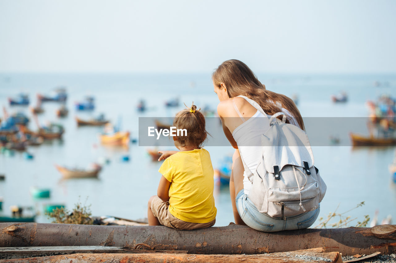 Rear View Of Mother With Daughter Sitting On Wood Against Sea