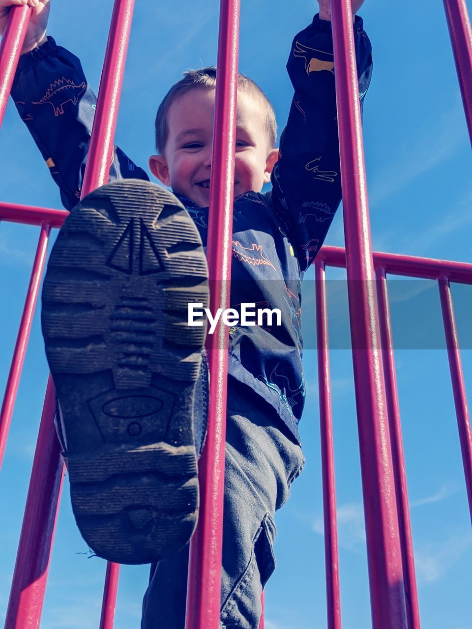LOW ANGLE VIEW OF BOY ON SLIDE