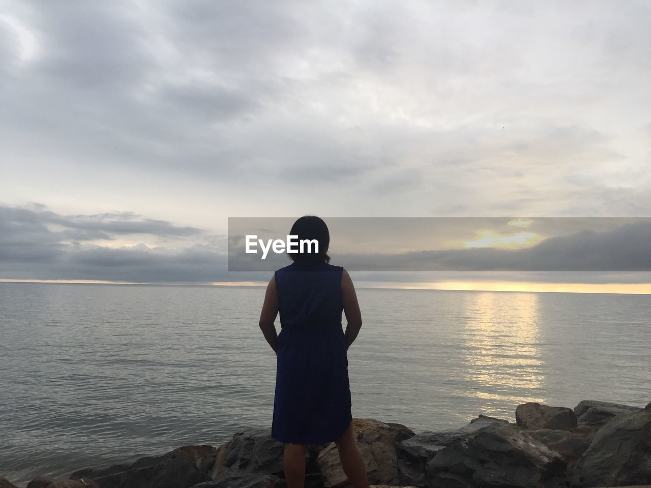 sea, sky, standing, horizon over water, water, sunset, nature, cloud - sky, scenics, beauty in nature, one person, tranquil scene, tranquility, rear view, real people, outdoors, day, people