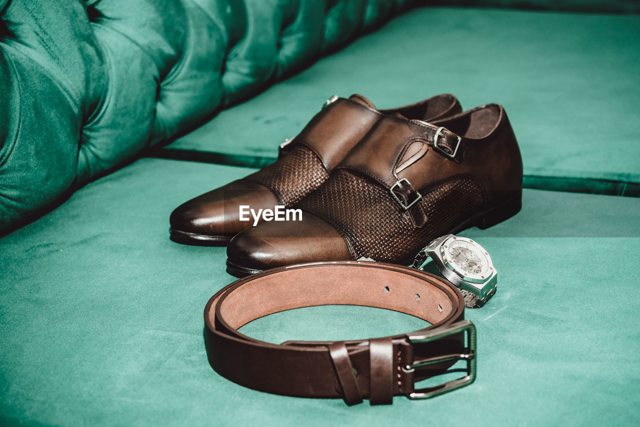 High angle view of shoes with belt and wristwatch on sofa