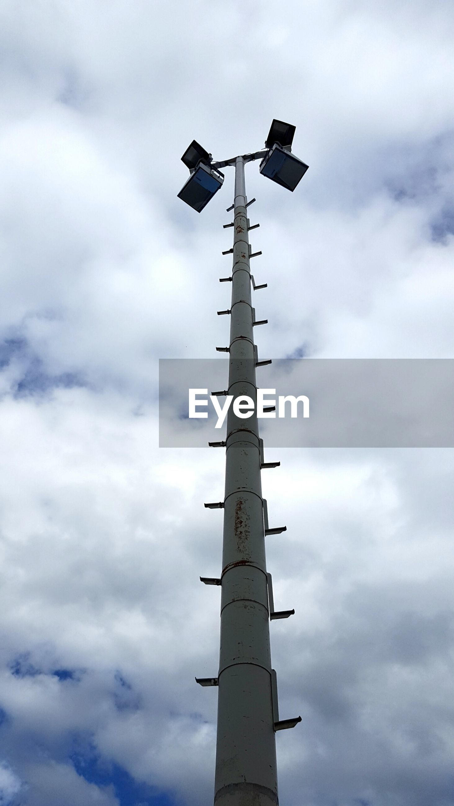 Low angle view of floodlights against cloudy sky
