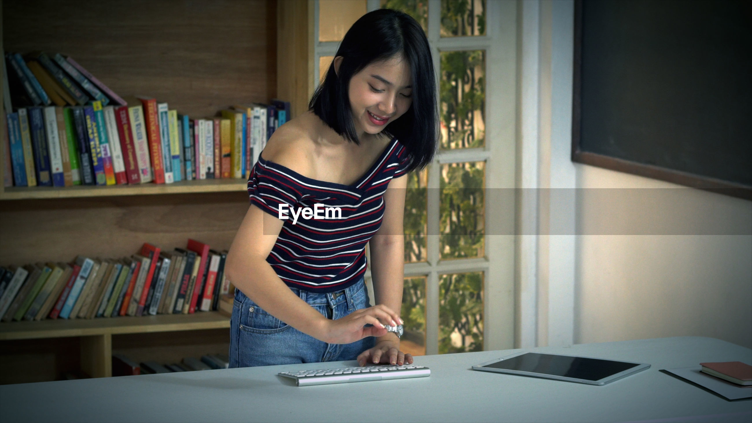 Smiling young woman using computer on table