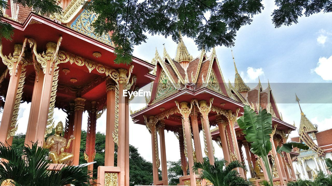 low angle view, architecture, religion, built structure, spirituality, place of worship, tree, day, outdoors, building exterior, architectural column, travel destinations, history, no people, sky, nature