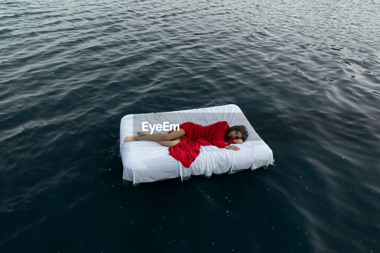 Young woman sleeping on bed floating in lake