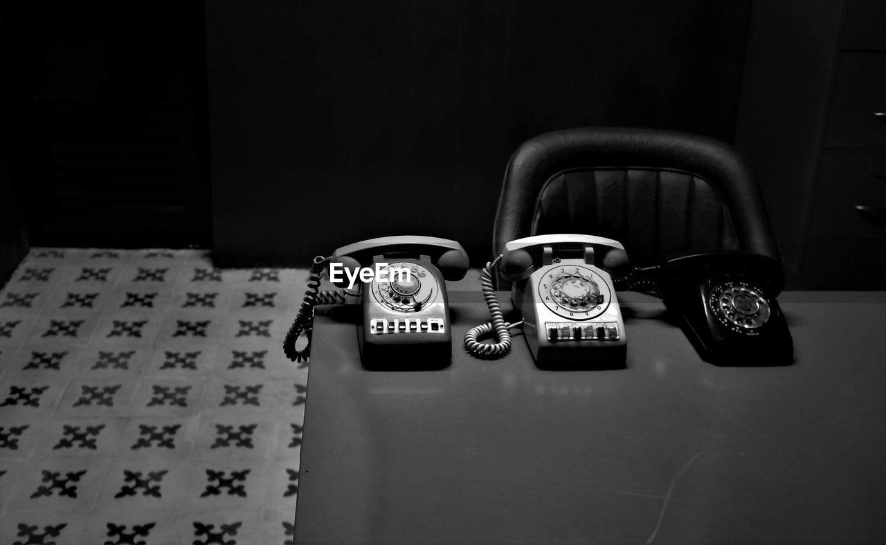 High angle view of telephones on table in darkroom