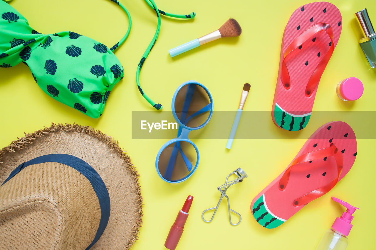 Directly above shot of vacation equipment on yellow background