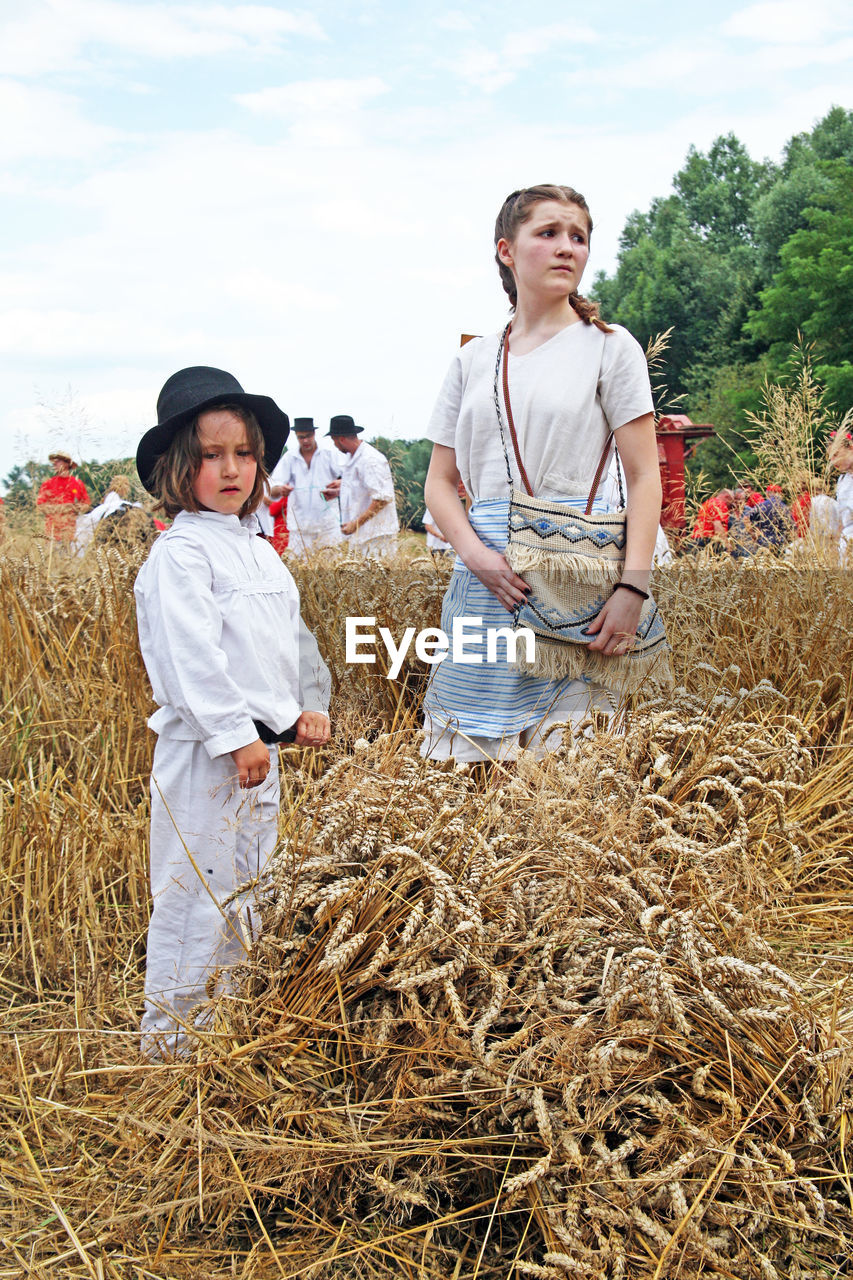 looking at camera, real people, casual clothing, standing, field, agriculture, portrait, straw, smiling, front view, togetherness, young women, hay, girls, day, young adult, young men, full length, outdoors, happiness, lifestyles, boys, rural scene, growth, childhood, nature, cereal plant, farmer, sky, people