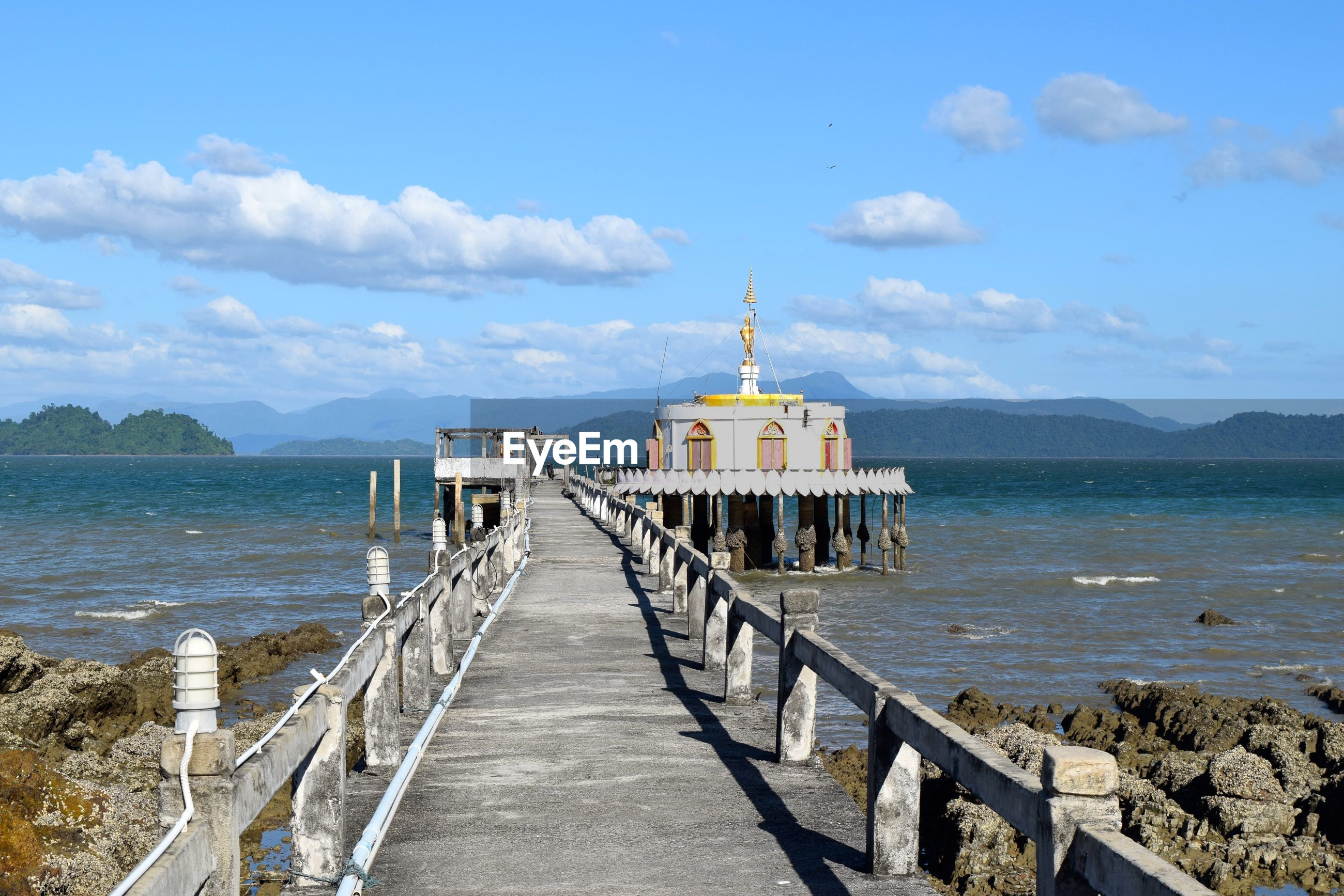 water, sea, the way forward, sky, built structure, architecture, pier, tranquil scene, tranquility, cloud - sky, leading, railing, mountain, scenics, building exterior, empty, cloud, blue, diminishing perspective, nature