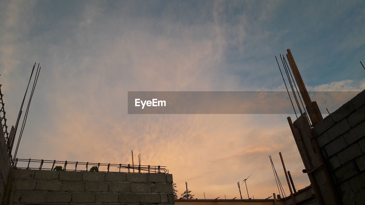 sky, architecture, built structure, cloud - sky, building exterior, low angle view, sunset, nature, no people, building, outdoors, construction site, crane - construction machinery, connection, city, construction industry, technology, industry, orange color, high section