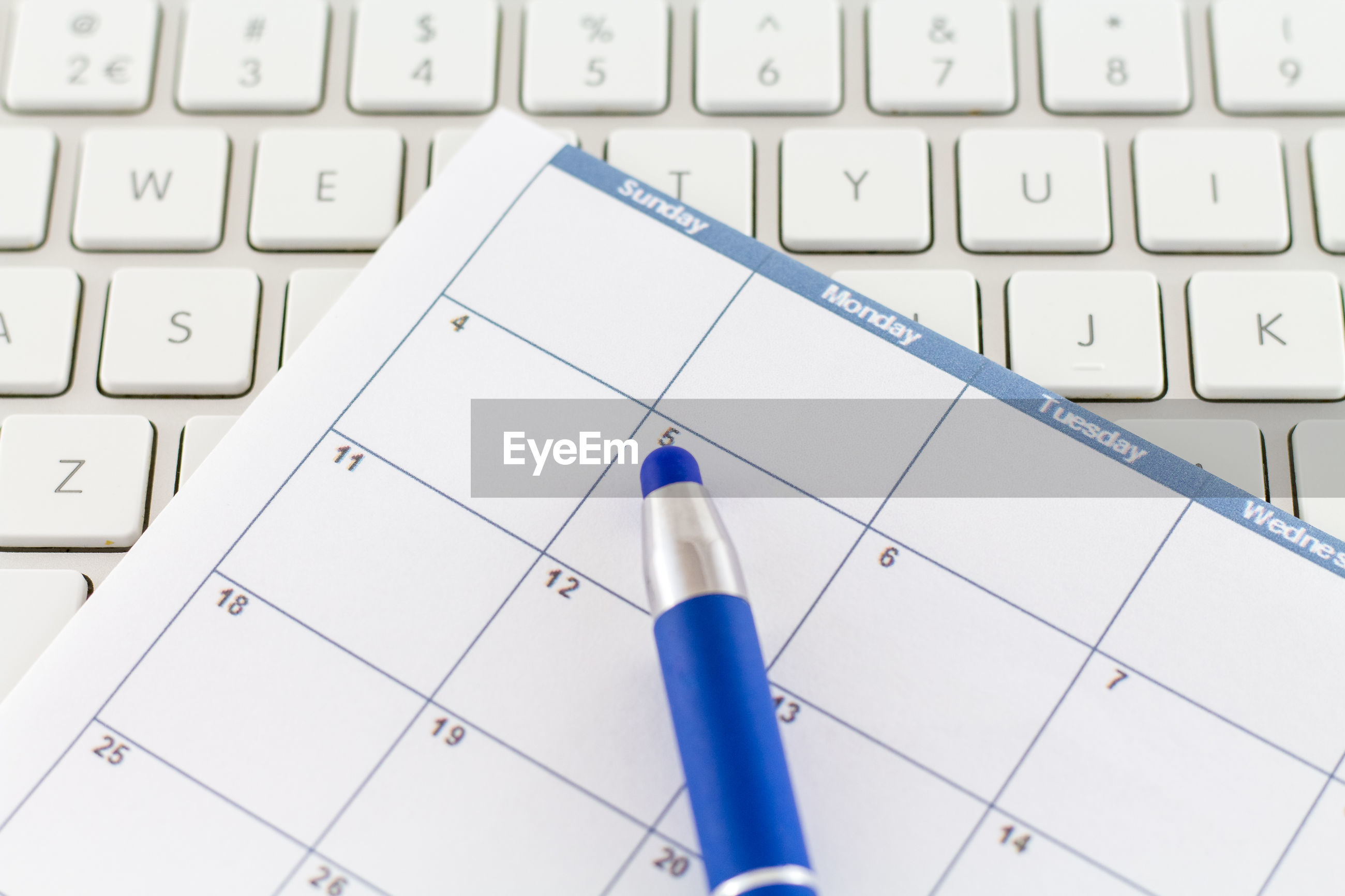 Close-up of pen and calendar on computer keyboard