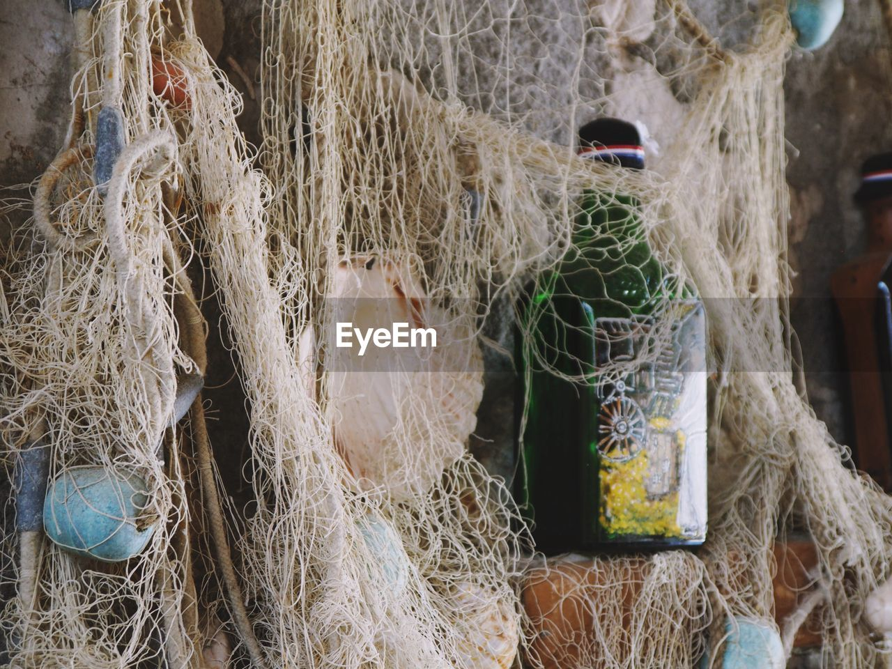 no people, fishing net, close-up, fishing industry, fishing, hanging, day, rope, commercial fishing net, backgrounds, outdoors, still life, string, full frame, for sale, rod, buoy, art and craft, white color, wall - building feature, complexity