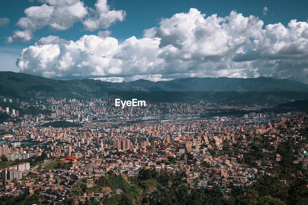 sky, city, cloud - sky, architecture, cityscape, building exterior, built structure, residential district, crowd, nature, building, crowded, mountain, high angle view, day, town, landscape, outdoors, environment, community, townscape, urban sprawl, settlement