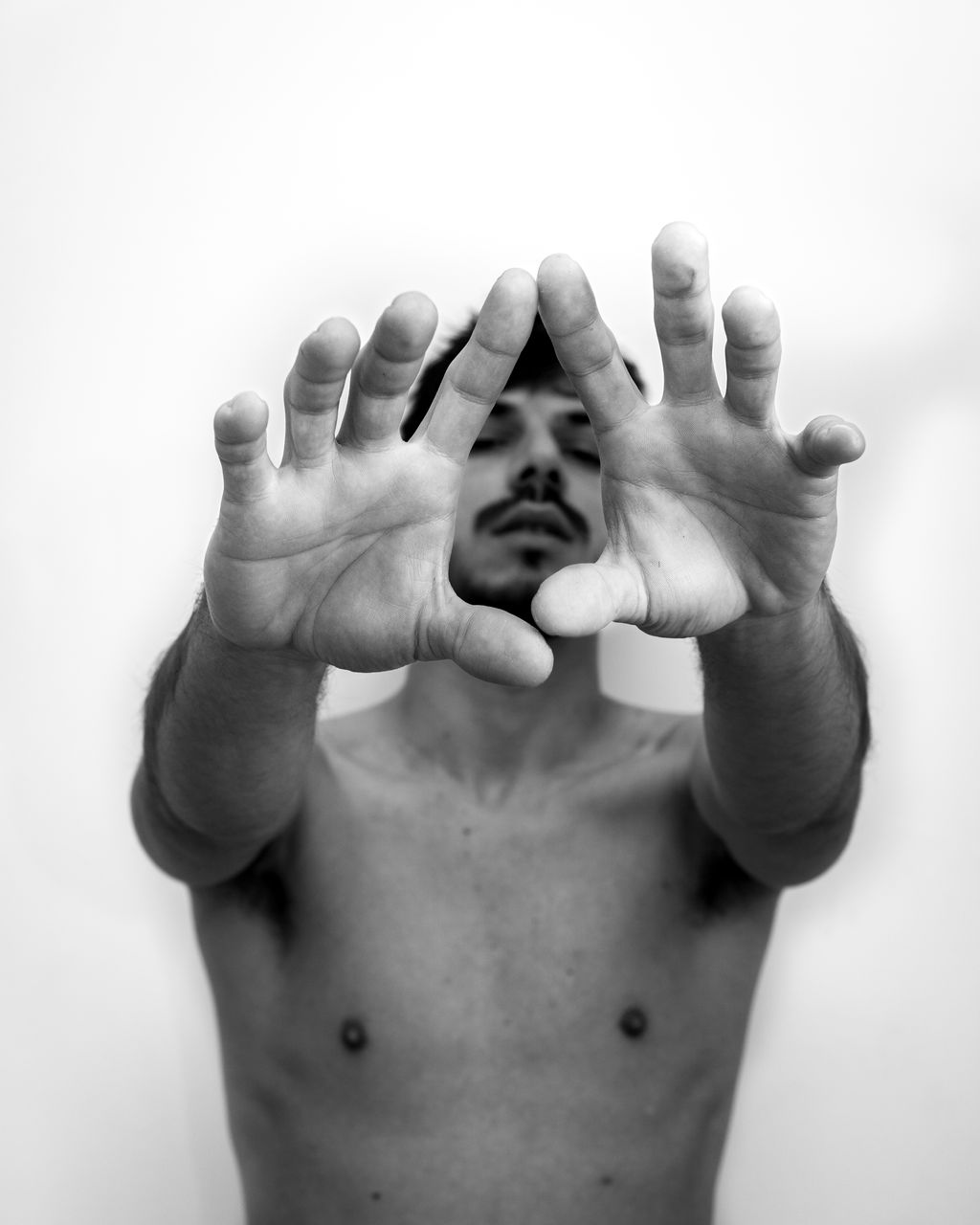 Portrait Of Shirtless Man Gesturing Against White Background