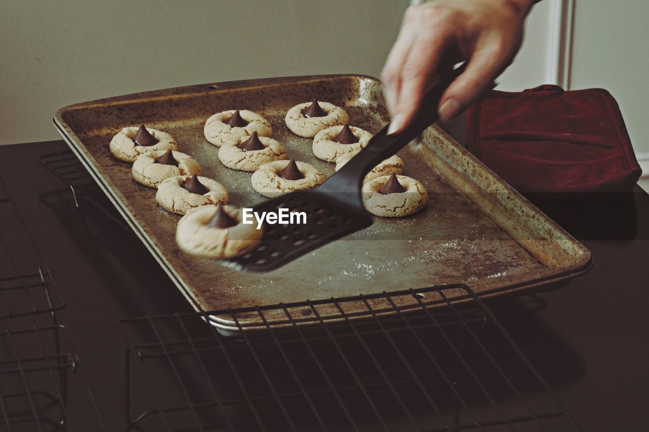 Cropped Hand Picking Cookie From Baking Sheet With Spatula