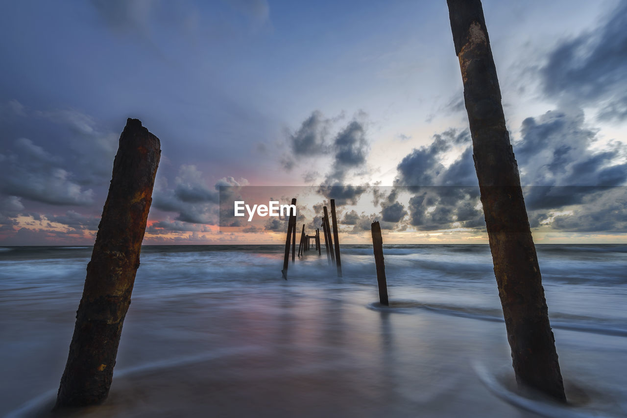 sky, cloud - sky, water, nature, sea, tranquility, beauty in nature, no people, sunset, scenics, outdoors, wooden post, tranquil scene, beach, horizon over water, day