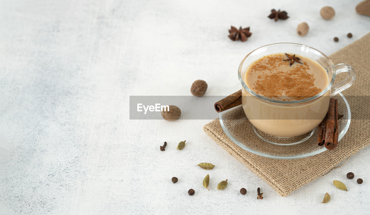 Traditional indian masala tea in a glass cup with cinnamon, ginger, cardamom, anise, honey, milk.