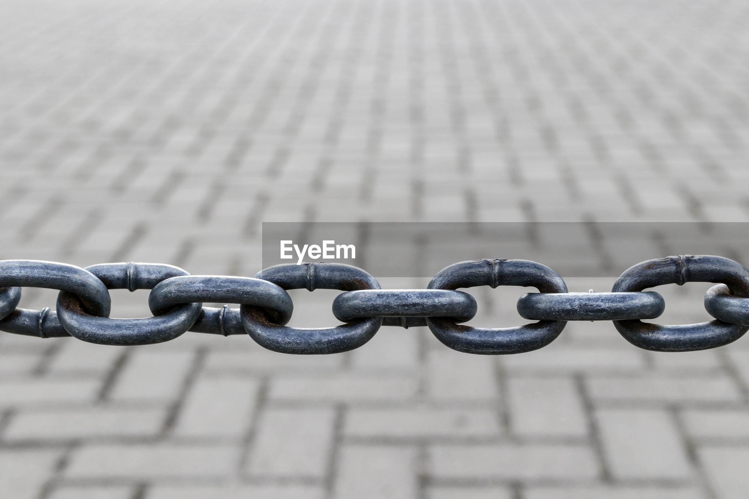 CLOSE-UP OF CHAIN ON METAL FENCE