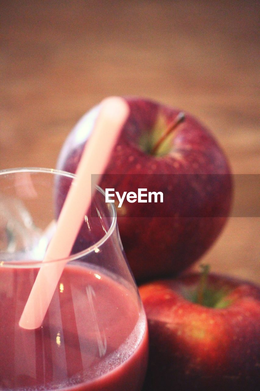 Close-up of juice served in glass by apples on table