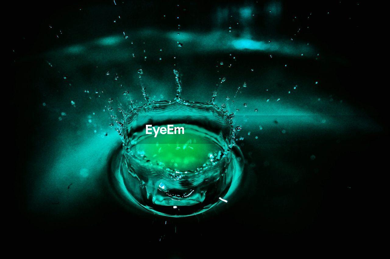 Close-Up Of Drop Splashing On Green Water