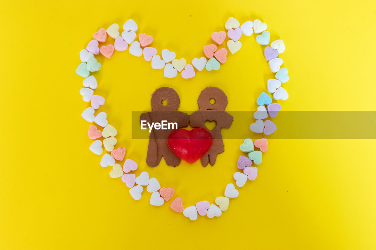 heart shape, indoors, yellow, love, studio shot, food and drink, still life, food, emotion, no people, creativity, directly above, close-up, positive emotion, art and craft, sweet food, freshness, colored background, arrangement, cookie, temptation