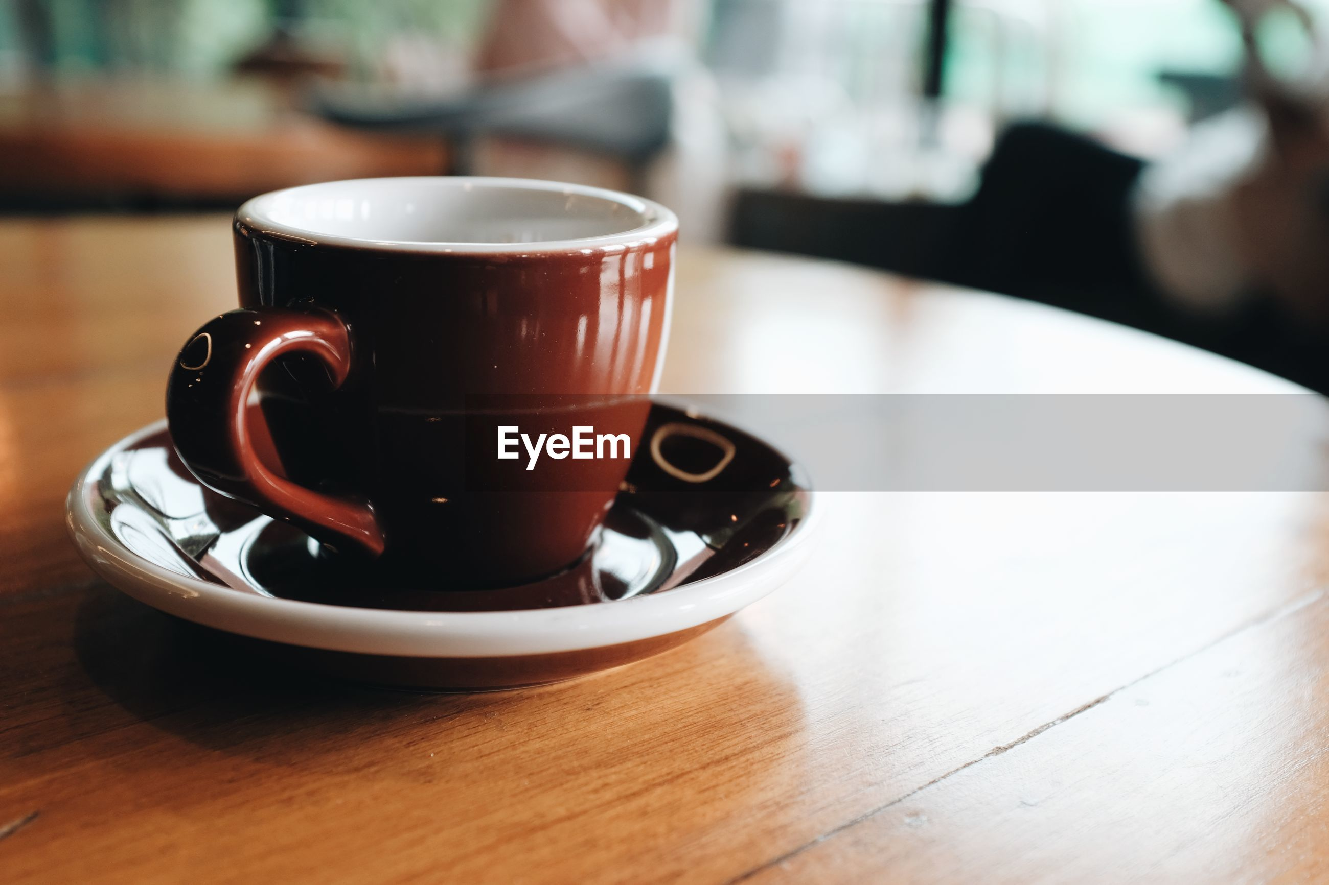 Close up view of a brown coffee cup on a wooden table in a coffee shop