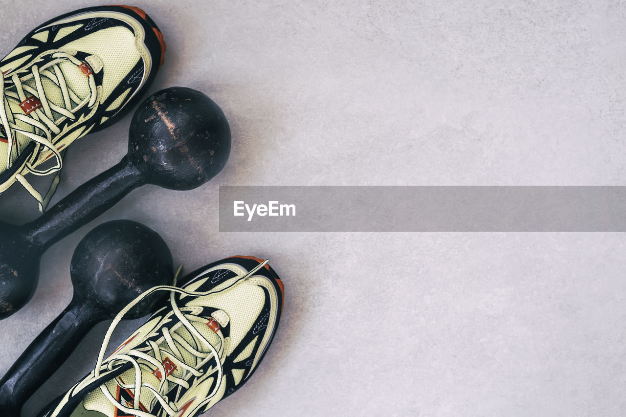 indoors, high angle view, no people, shoe, still life, sport, close-up, directly above, copy space, shoelace, sports equipment, black color, body part, studio shot, ball, flooring, healthy lifestyle, canvas shoe, small group of objects