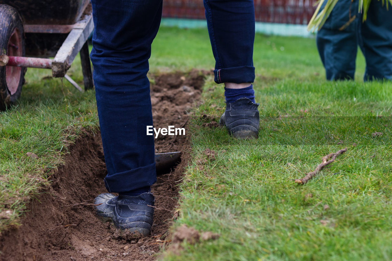Low Section Of Man Digging Dirt In Yard