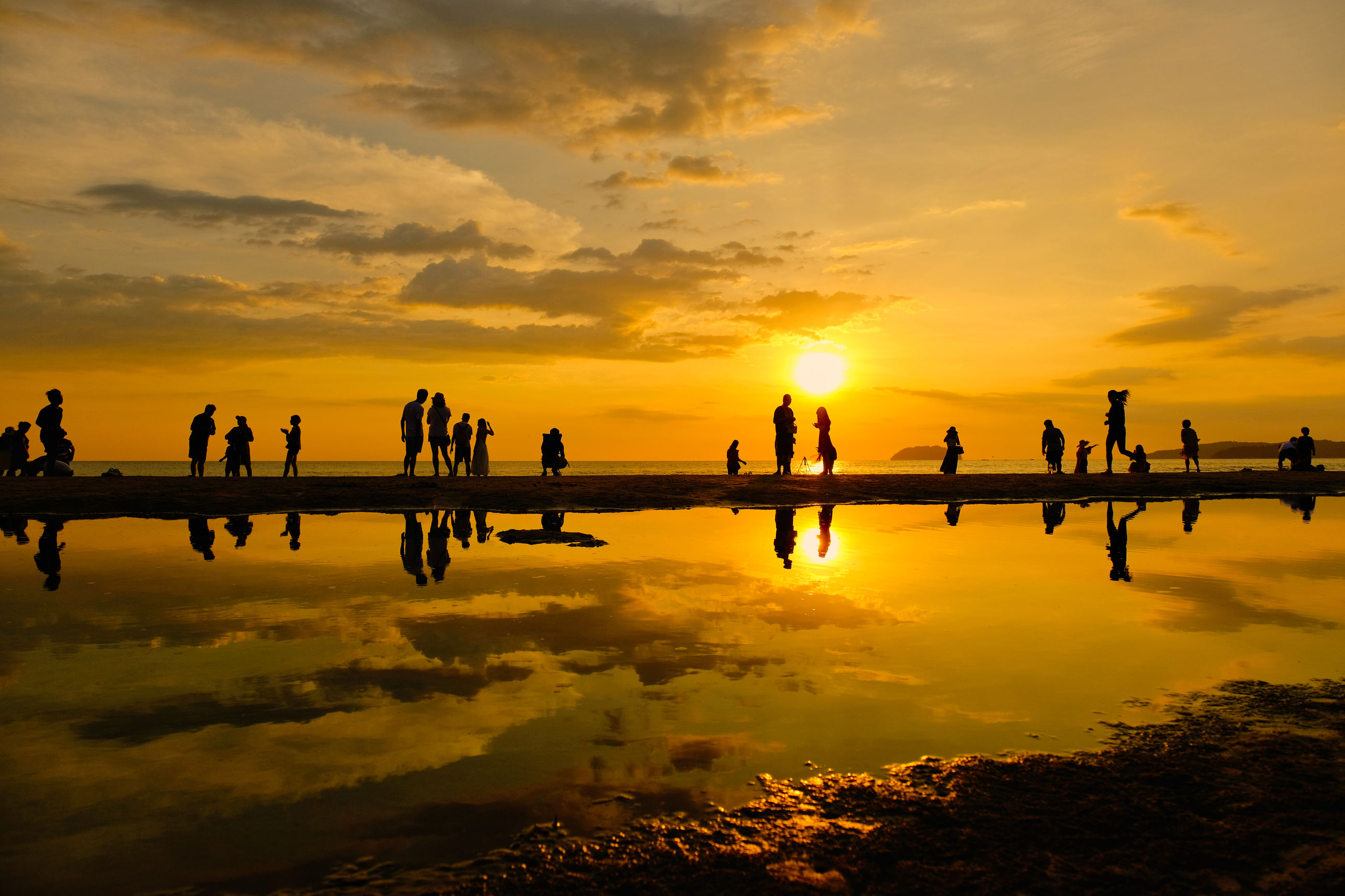 Silhouette people standing against sea during sunset