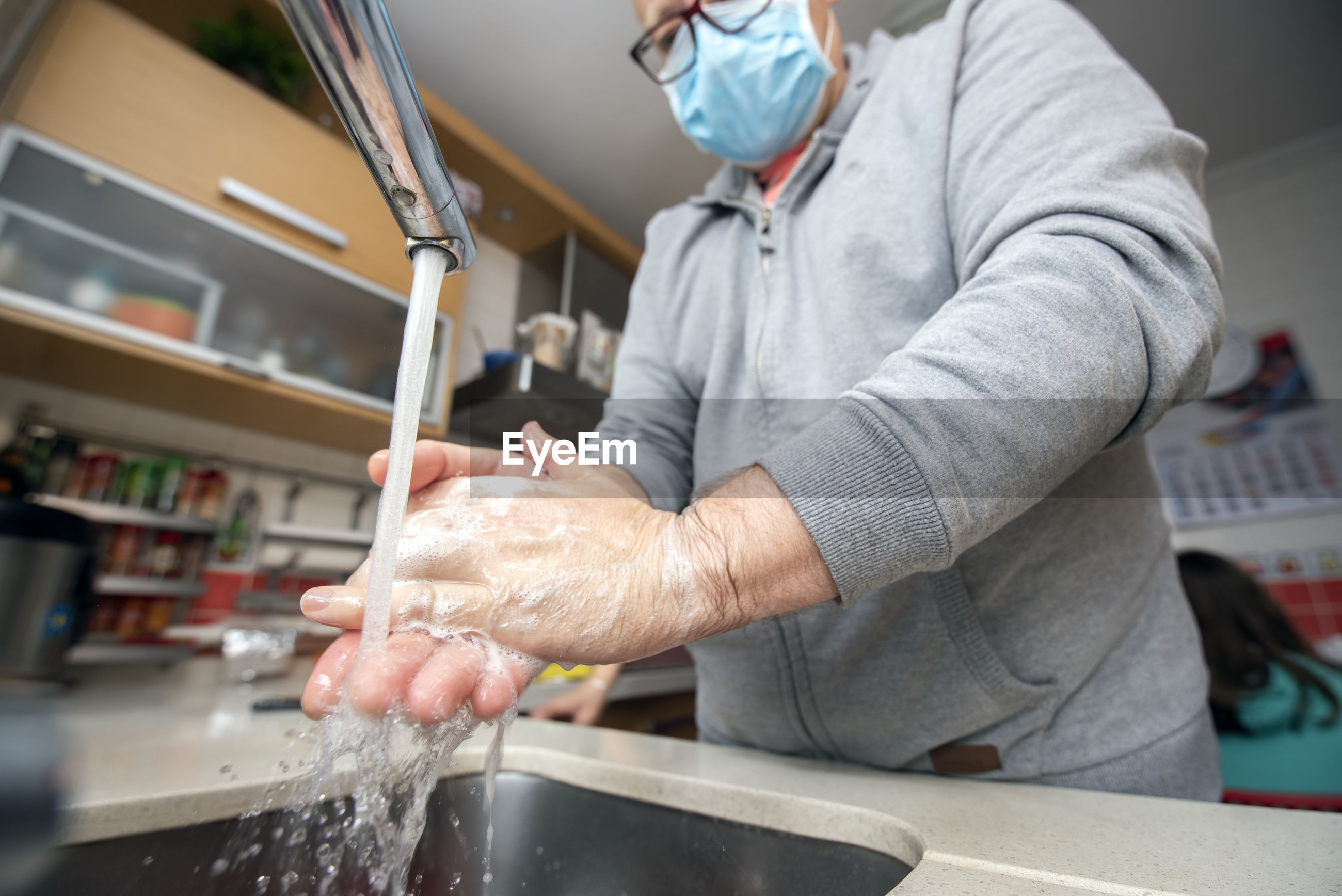 Midsection of man washing hands in sink