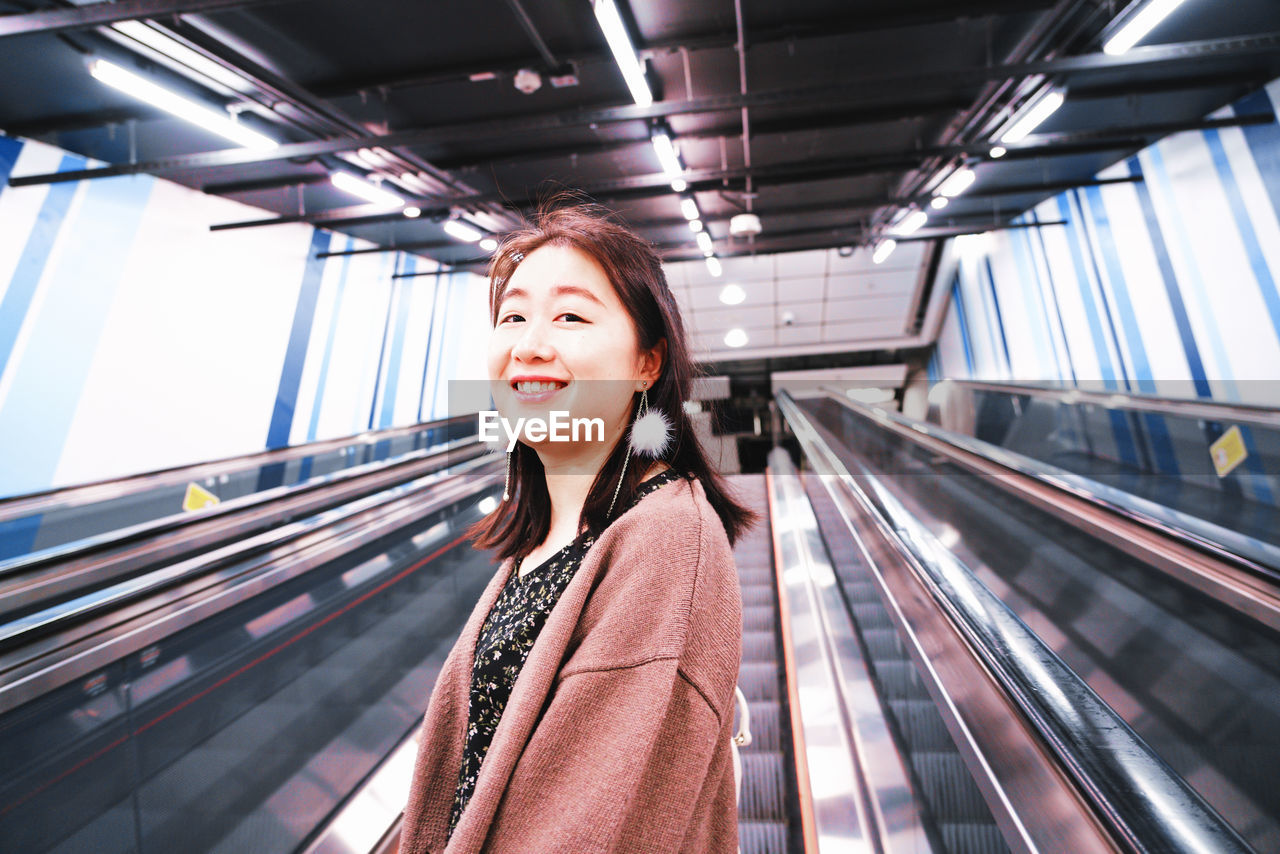 PORTRAIT OF A SMILING YOUNG WOMAN ON ESCALATOR