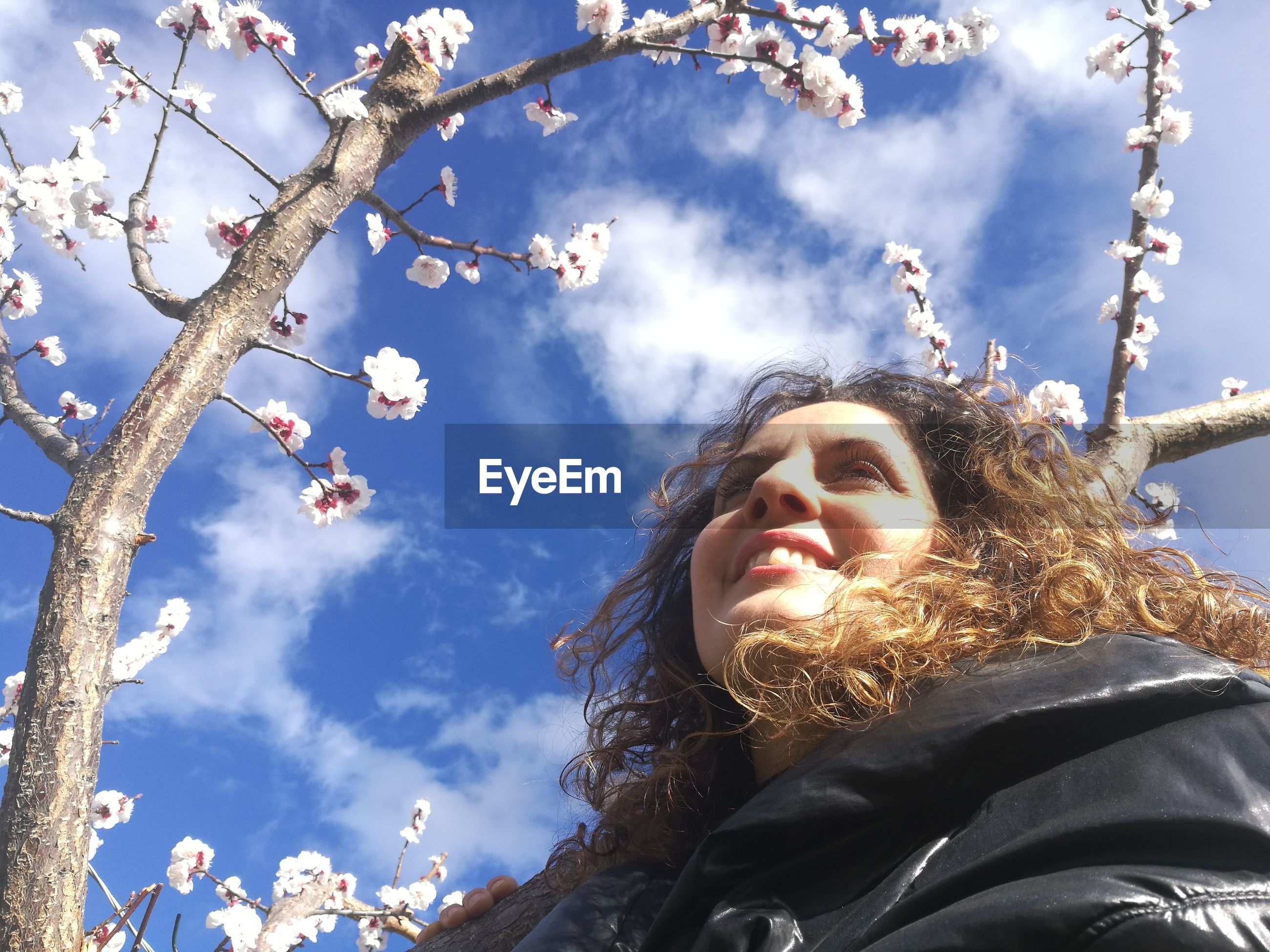 Low angle view of woman by cherry blossoms against sky