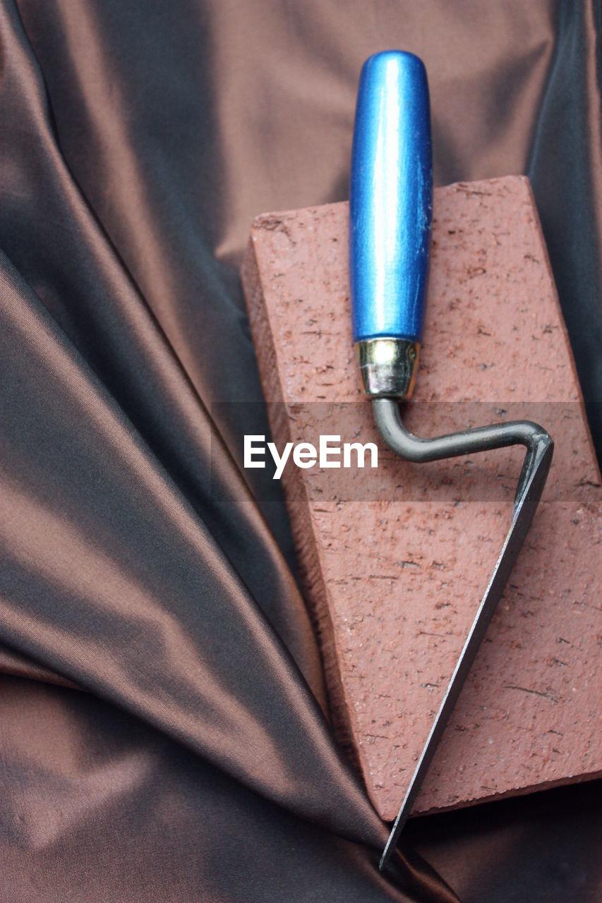 High angle view of hand tool on brick