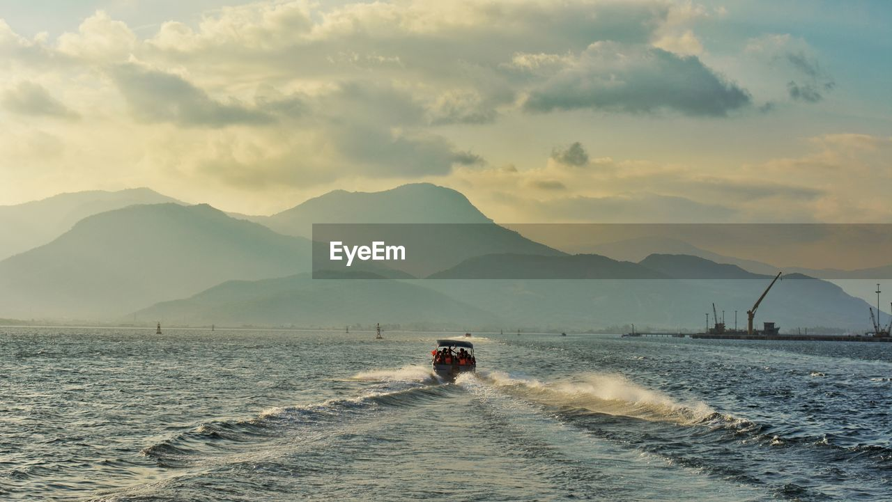 Boat Sailing In Sea With Silhouette Mountains In Background Against Cloudy Sky