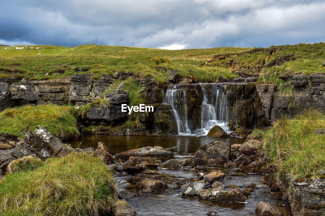 cloud - sky, scenics - nature, water, sky, beauty in nature, environment, rock, waterfall, nature, flowing water, solid, day, rock - object, long exposure, motion, no people, plant, tranquil scene, blurred motion, flowing, outdoors, power in nature