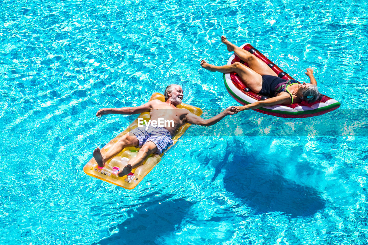 water, swimwear, men, pool, adult, swimming pool, trip, vacations, holiday, males, emotion, full length, couple - relationship, women, nature, heterosexual couple, fun, enjoyment, positive emotion, floating on water, flirting